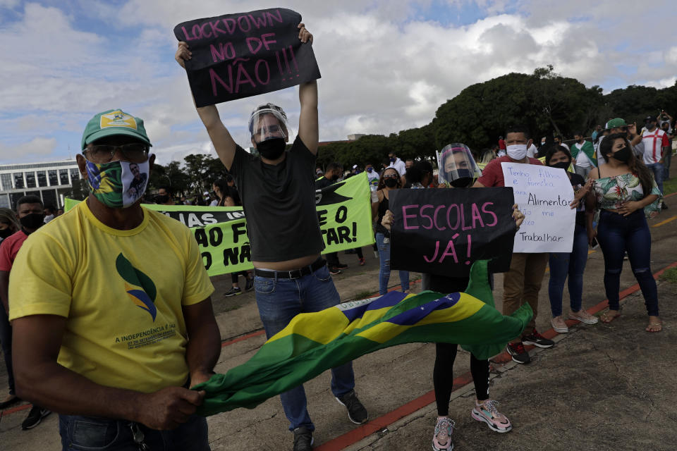 """Demonstrators hold up Portuguese messages like """"No lockdown!"""" and """"Schools now!"""" on the first day of a two-week-long lockdown to curb the spread of COVID-19 in Brasilia, Brazil, Monday, March. 1, 2021. It's the second lockdown since the start of the pandemic one year ago. (AP Photo/Eraldo Peres)"""