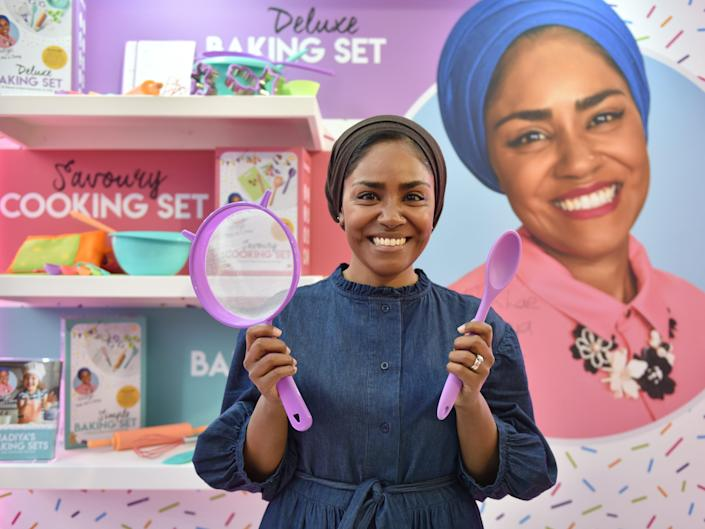 Nadiya Hussain, winner of GBBO, holds up items from her toy cooking set in 2020.