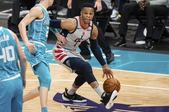 Washington Wizards guard Russell Westbrook (4) drives to the basket while guarded by Charlotte Hornets guard LaMelo Ball (2) during the first half of an NBA basketball game in Charlotte, N.C., Sunday, Feb. 7, 2021. (AP Photo/Jacob Kupferman)