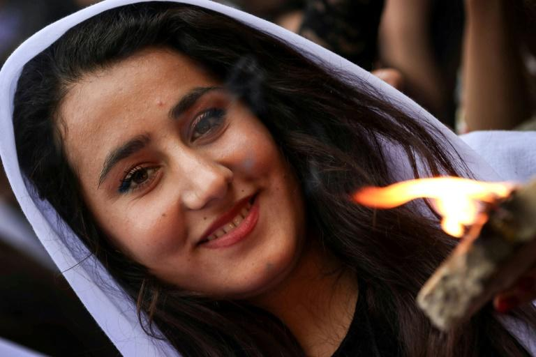 An Iraqi Yazidi woman carries a paraffin torch outside Lalish temple, the holiest shrine of her faith, on April 18, 2017, on the eve of Yazidi New Year