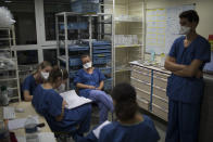 At the end of her shift, 26-year-old Nurse Pauline Reynier, center left, updates the night shift nurses on the statuses of COVID-19 patients in a makeshift ICU at the La Timone hospital in Marseille, southern France, Thursday, Nov. 12, 2020. (AP Photo/Daniel Cole)