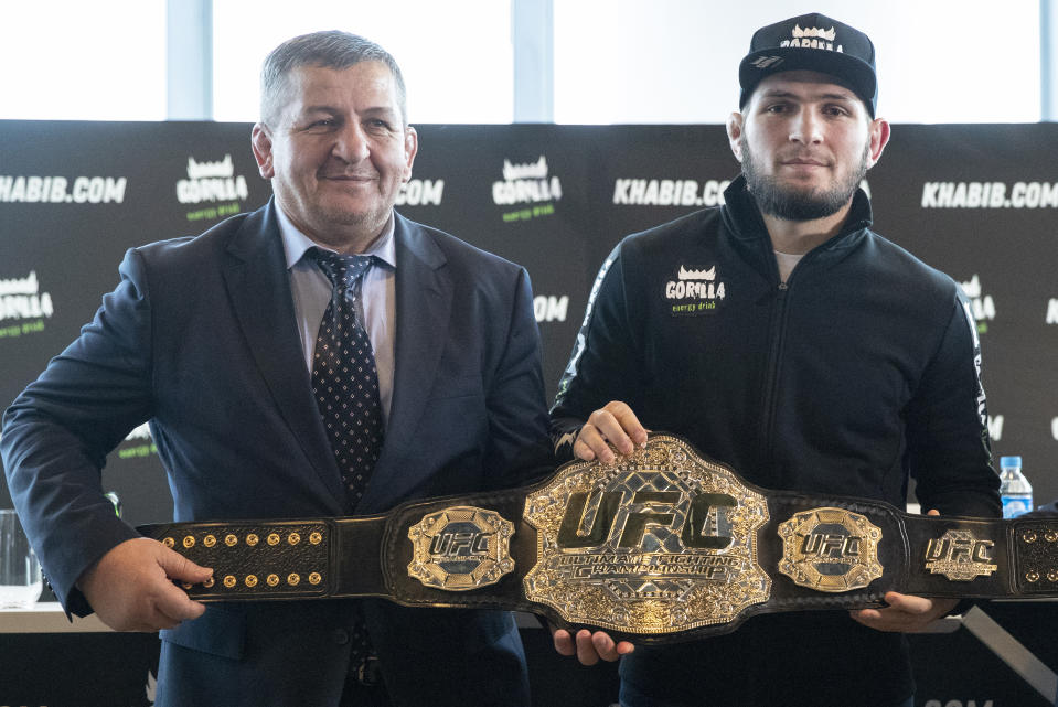 UFC lightweight champion Khabib Nurmagomedov, right, and his father Abdulmanap Nurmagomedov pose with the trophy belt during a news conference in Moscow, Russia, Monday, Nov. 26, 2018. The Russian professional mixed martial arts fighter Nurmagomedov, said he can imagine a reconciliation with Conor McGregor after the bitter feud around last month's title fight, but said he would like to fight Floyd Mayweather Jr.  (AP Photo/Pavel Golovkin)