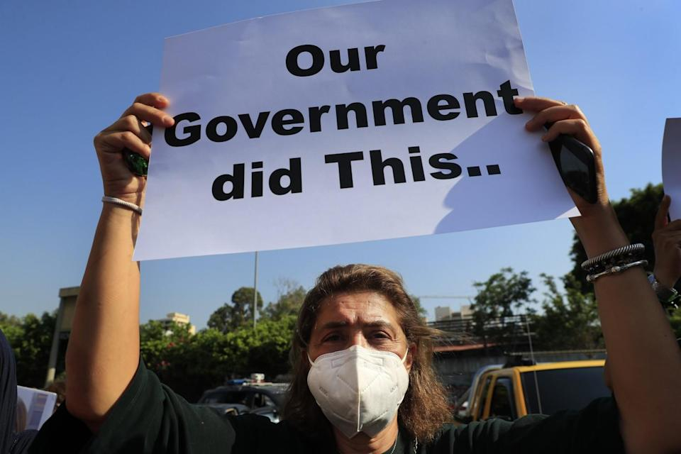 """A person in a mask holds up a sign that says """"Our government did this."""""""