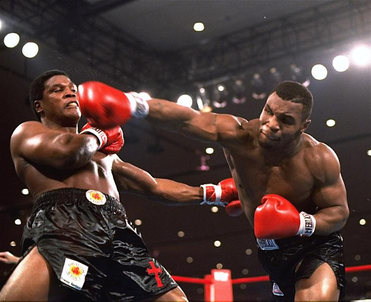 FILE - In this Nov. 22, 1986, file photo, Mike Tyson, right, delivers a blow to Trevor Berbick during a boxing bout in Las Vegas. Organizers say seven boxers and 12 others will be the first inductees at the new Nevada Boxing Hall of Fame in Las Vegas. Inductees to be enshrined Saturday, Aug. 10, 2013, in the inaugural class include boxers Tyson, Larry Holmes, Sugar Ray Leonard, Julio Cesar Chavez, Mike McCallum, Diego Corrales and Oscar De La Hoya. (AP Photo/Douglas C. Pizac, File)