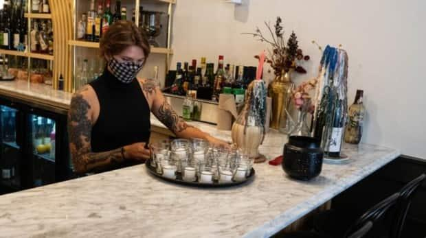 A staff member at Ottawa's Arlo restaurant sets up a tray of tea lights as outdoor dining is now allowed in Ontario. Indoor dining returns under Step 3 of the reopening plan. (Jean Delisle/CBC - image credit)