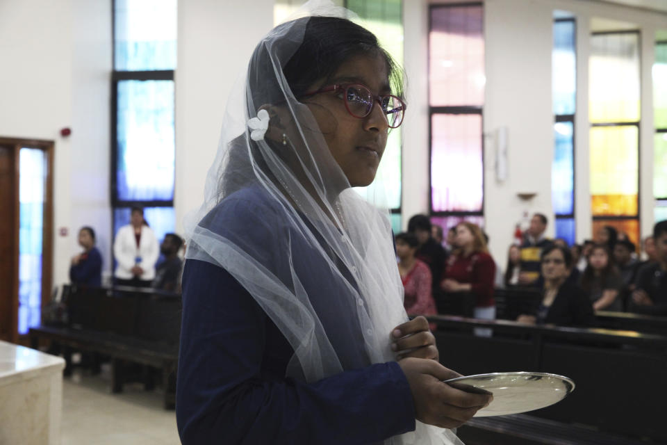 In this Sunday, Jan. 20, 2019 photo, a young girl holds a communion plate during Mass at St. Mary's Catholic Church in Dubai, United Arab Emirates. Pope Francis' visit from Feb. 3 through Feb. 5 marks the first papal visit in history to the Arabian Peninsula, the birthplace of Islam. A diverse and international flock awaits him. The Catholic Church believes there are some 1 million Catholics in the UAE today. (AP Photo/Jon Gambrell)