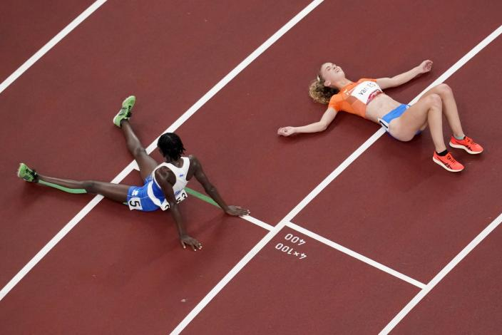 Alex Rose, of Samoa, and Diane Van Es, of Netherlands, colapse after competing during the first round of the women's 5,000-meter at the 2020 Summer Olympics, Friday, July 30, 2021, in Tokyo. (AP Photo/Morry Gash)