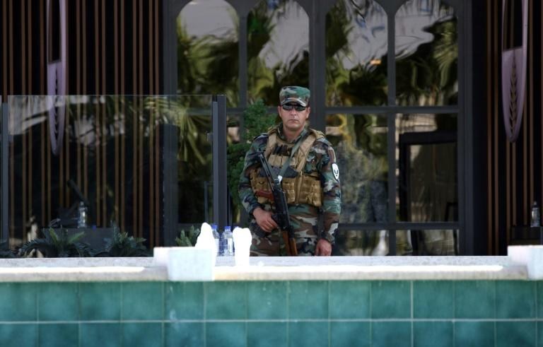A member of the Iraqi Kurdish security forces stands guard outside the restaurant where two people were shot dead in Arbil