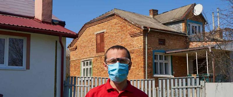 man in medical mask in the yard,man standing in his yard in summer wearing a protective mask and goggles