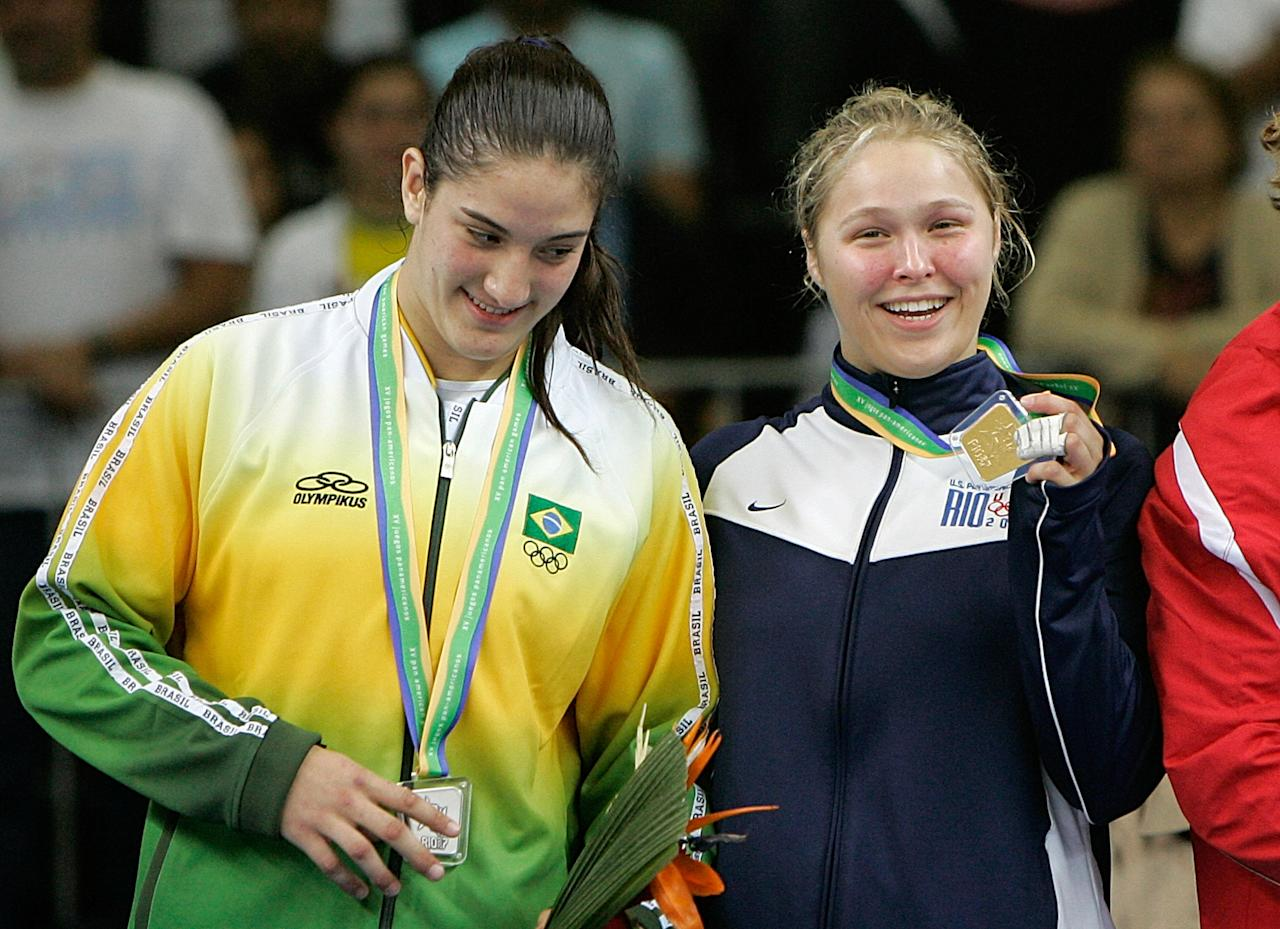 U.S. Ronda Rousey, right, shows her gold medal as Brazil's Mayra Silva stands with her on the winner's podium for the Judo Women's -70 kg middle competition at the Pan American Games in Rio de Janeiro, Friday, July 20, 2007. (AP Photo/Silvia Izquierdo)
