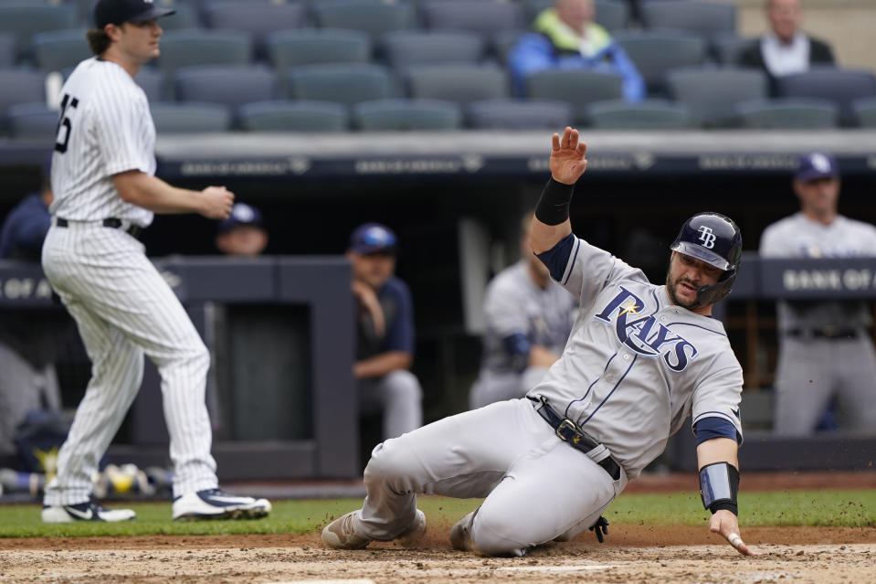 Tampa Bay Rays Mike Zunino, right, slides in to score as New York Yankees starting pitcher Gerrit Cole, left, backs up the late throw from right field during the fifth inning of a baseball game, Thursday, June 3, 2021, at Yankee Stadium in New York. (AP Photo/Kathy Willens)