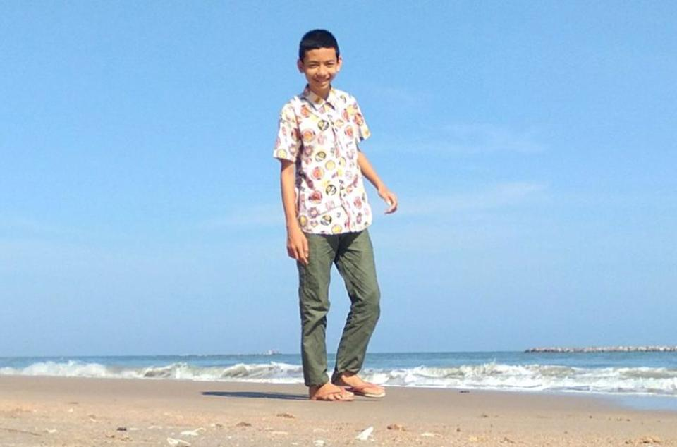 Piyawat Harikun, 17, is pictured walking on a beach.