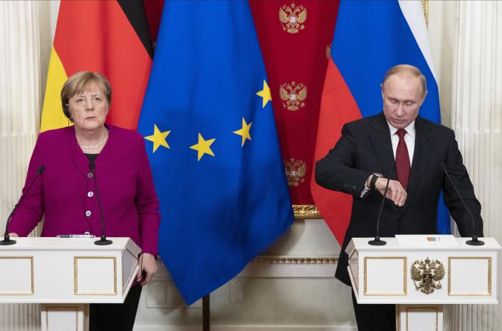 German Chancellor Angela Merkel listens to a journalist's question as Russian President Vladimir Putin looks at his watch during their joint news conference following their talks in the Kremlin in Moscow, Russia, Saturday, Jan. 11, 2020. Merkel visits Moscow to discuss current international issues such as the situation in Syria, Libya, Ukraine, US-Iran tensions, as well as bilateral relations. (AP Photo/Pavel Golovkin, Pool)