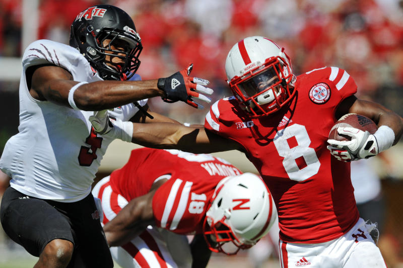 """FILE - This Sept. 15, 2012 file photo shows Nebraska's Ameer Abdullah (8) stiff-arming Arkansas State's Don Jones, left, in the second half of their NCAA college football game in Lincoln, Neb. Nebraska offensive coordinator Tim Beck warns if the Cornhuskers have an emotional hangover from their 39-point Big Ten championship game loss, """"it's going to get ugly"""" when they play sixth-ranked Georgia in the Capital One Bowl. (AP Photo/Dave Weaver, File)"""