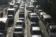 A woman crosses a highway as traffic builds up near a checkpoint during a stricter lockdown as a precaution against the spread of the coronavirus on the outskirts of Marikina City, Philippines on Friday, August 6, 2021. Thousands of people jammed coronavirus vaccination centers in the Philippine capital, defying social distancing restrictions, after false news spread that unvaccinated residents would be deprived of cash aid or barred from leaving home during a two-week lockdown that started Friday. (AP Photo/Basilio Sepe)