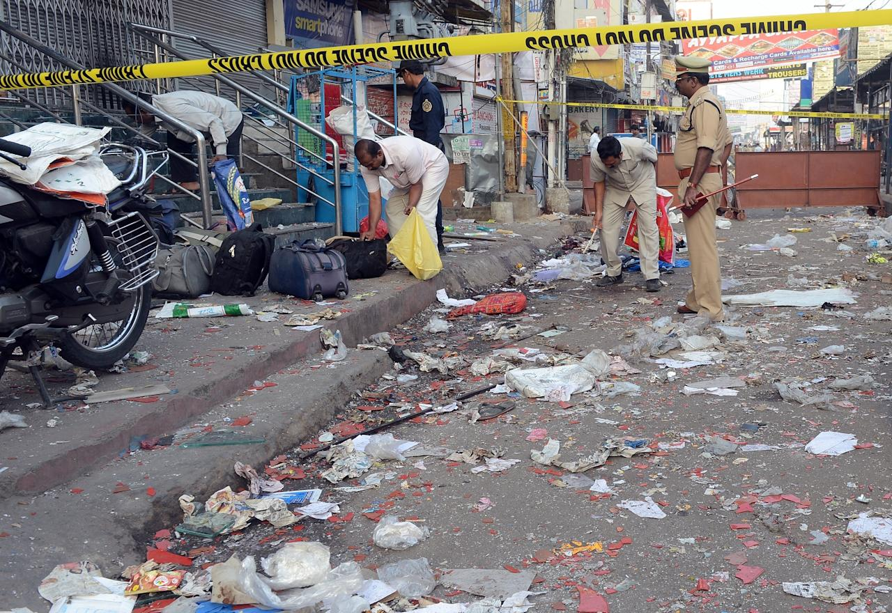Policemen search among the debris at one of the blast sites at Dilsukh Nagar in Hyderabad on February 22, 2013. India hunted for perpetrators of twin bomb attacks that killed 14 people and wounded dozens more near a cinema and a bus stand in a busy neighbourhood in the city of Hyderabad. The bombings, the first to hit India since 2011, hit a mainly Hindu district in Hyderabad, a hub of India's computing industry which hosts local offices of Google and Microsoft among others and which has a large Muslim population.   AFP PHOTO/Indranil MUKHERJEE