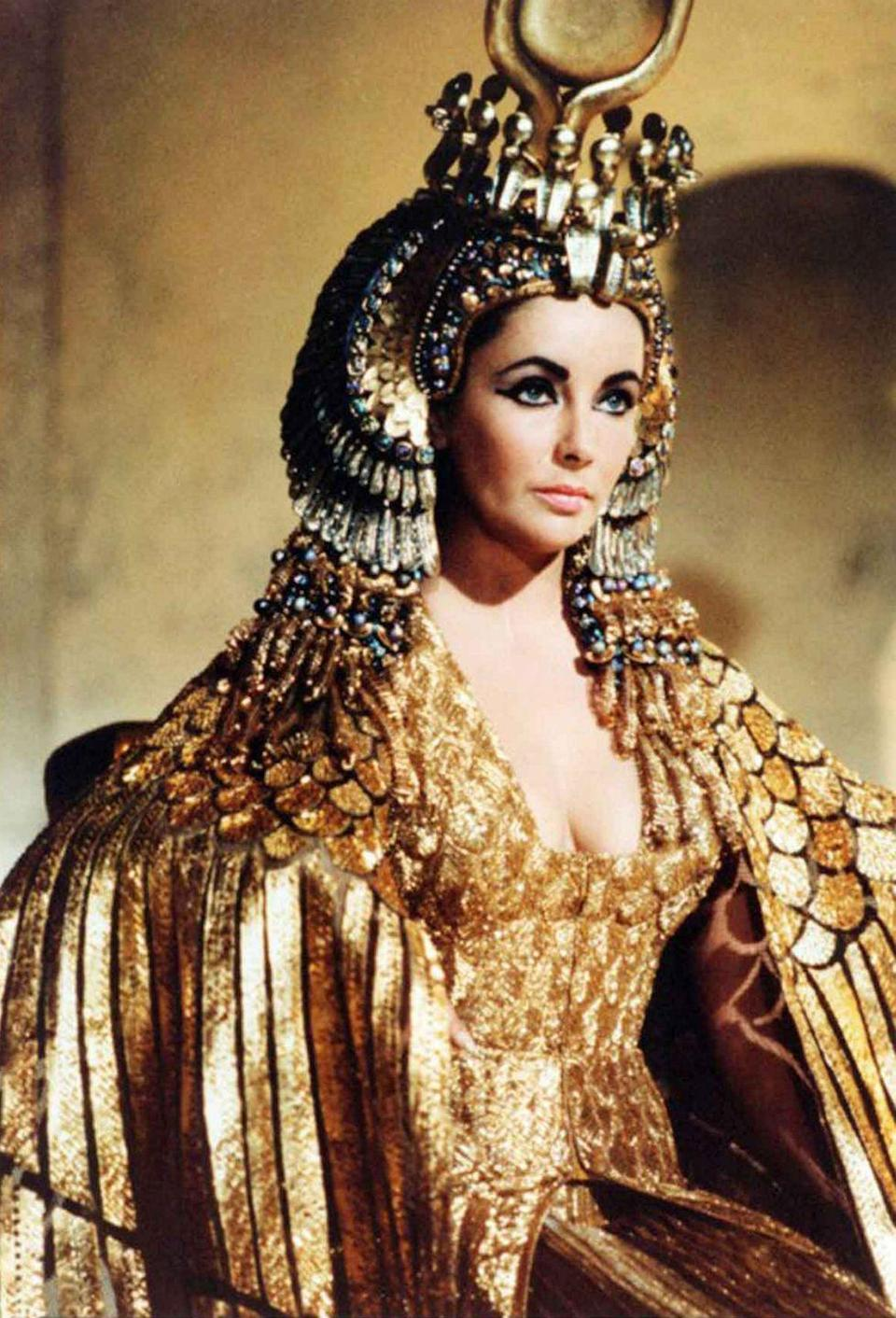 """<p>There are so many things to note about <em>Cleopatra</em>—from Elizabeth Taylor's budding romance with costar Richard Burton to the film's elaborate set and <a href=""""https://variety.com/2017/film/news/most-expensive-movie-pirates-of-the-caribbean-cleopatra-avatar-hollywood-budgets-1202434333/"""" rel=""""nofollow noopener"""" target=""""_blank"""" data-ylk=""""slk:overextended budget"""" class=""""link rapid-noclick-resp"""">overextended budget</a>. But the one thing that is undeniable is the amazing wardrobe designed for Taylor, starting with the 24-karat gold headdress and cape she wore while arriving in Rome. </p>"""