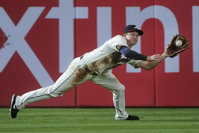 Atlanta Braves left fielder Elliot Johnson makes a catch in centerfield on a fly ball off the bat of Miami Marlins' Placido Polanco during the fourth inning of a baseball game, Saturday, Aug. 31, 2013, in Atlanta. (AP Photo/John Amis)