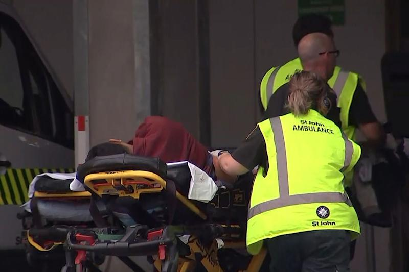 Authorities assist a victim of the New Zealand mosque shooting Friday