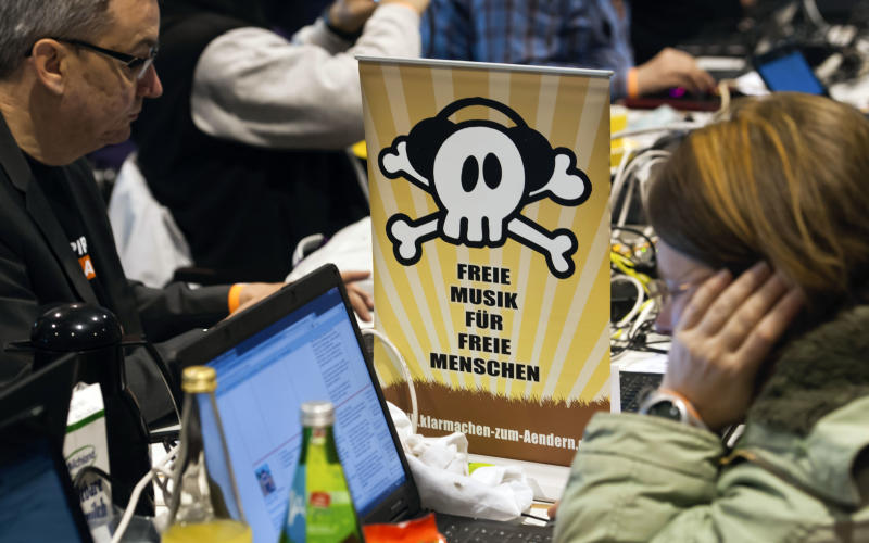 """Members of the Pirates party sit next to a poster reading """"Free Music for Free People"""" during their party convention in Neumuenster, northern Germany, Saturday, April 28, 2012. Pirates are capturing Germany's political system: The party started as a marginal club of computer nerds and hackers, but its appeal as an anti-establishment movement has lured many young voters to the ballot boxes, gaining it parliamentary seats in two consecutive state elections. (AP Photo/dapd, Clemens Bilan)"""