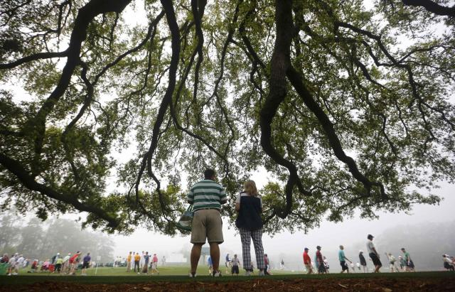 Golf patrons wander the foggy grounds during player practice rounds ahead of the 2015 Masters at Augusta National Golf Course in Augusta