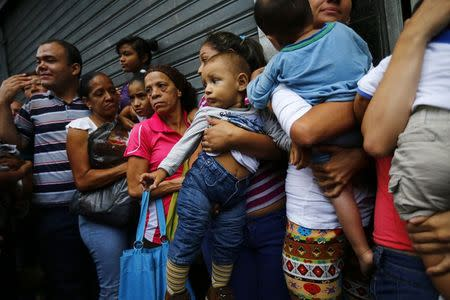 People line up to buy toilet paper and baby diapers at a supermarket in downtown Caracas