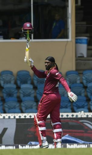 Chris Gayle of West Indies waves to fans while walking off the field