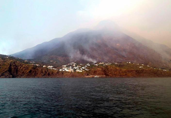 Smoke billows from the volcano on the Italian island of Stromboli, Wednesday, July 3, 2019. The news agency ANSA says that some 30 tourists jumped into the sea out of fear after a series of volcano erupted on the Sicilian island of Stromboli. Civil protection authorities said a hiker was confirmed killed by the eruptions Wednesday. (ANSA VIA AP) ORG XMIT: ROM104