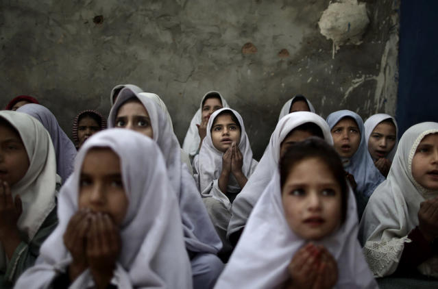 <p>Pakistani schoolgirls, who were displaced with their families from Pakistan's tribal areas due to fighting between militants and the army, chant prayers during a class to pay tribute for five female teachers and two aid workers who were killed by gunmen at a school in a slum on the outskirts of Islamabad, Pakistan, Jan. 3, 2013. Gunmen in northwest Pakistan killed five female teachers and two aid workers on Tuesday in an ambush on a van carrying workers home from their jobs at a community center, officials said. (Photo: Muhammed Muheisen/AP) </p>
