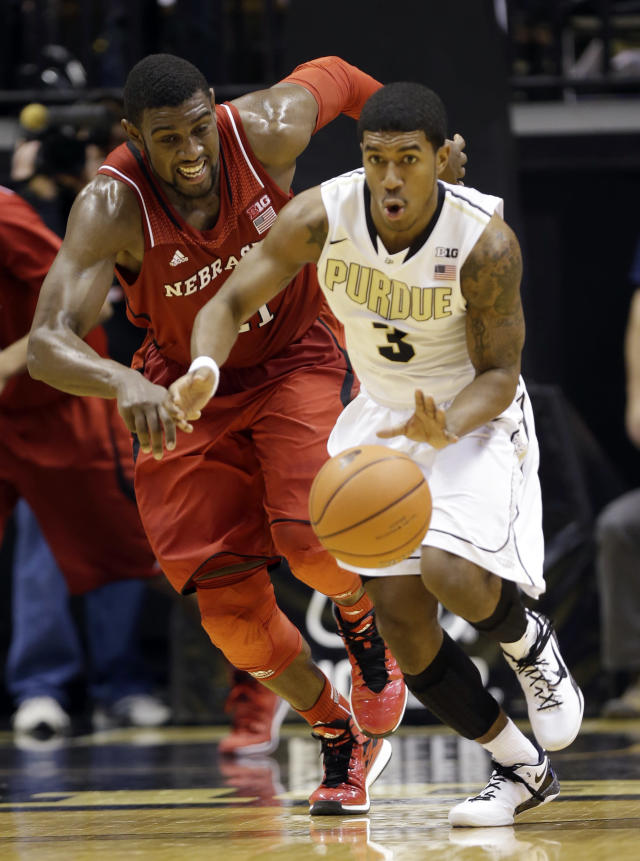 Purdue guard Ronnie Johnson, right, picks up a loose ball in front of Nebraska forward Leslee Smith in the second half of an NCAA college basketball game in West Lafayette, Ind., Sunday, Jan. 12, 2014. Purdue defeated Nebraska 70-64. (AP Photo/Michael Conroy)