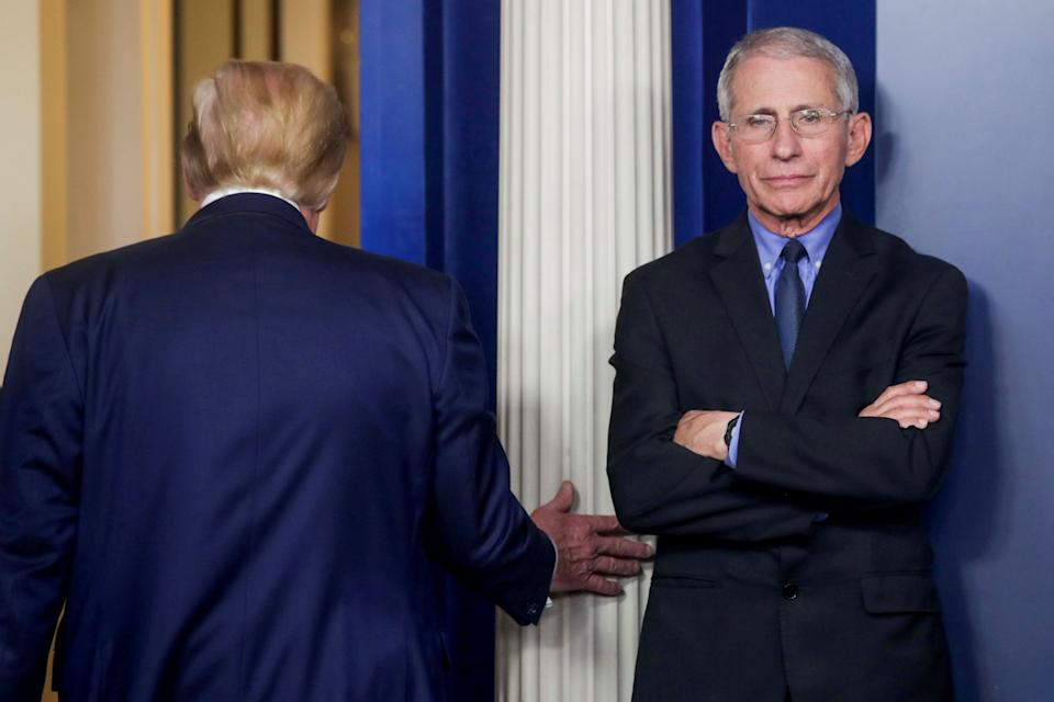 President Donald Trump is seen following a coronavirus task force daily briefing in March as Fauci stands by. (Photo: Jonathan Ernst/Reuters)
