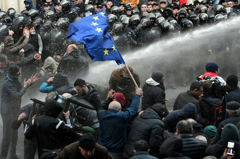 Riot police fire water cannons to break up a crowd of protesters outside the parliament building in Tbilisi