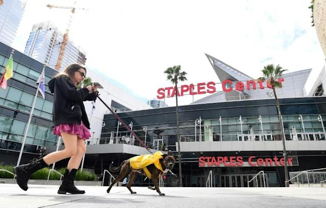 A woman walks her dog past a deserted Staples Center in Los Angeles, California as the Los Angeles Lakers announced that two of their players have tested positive for the coronavirus (AFP Photo/Frederic J. BROWN)