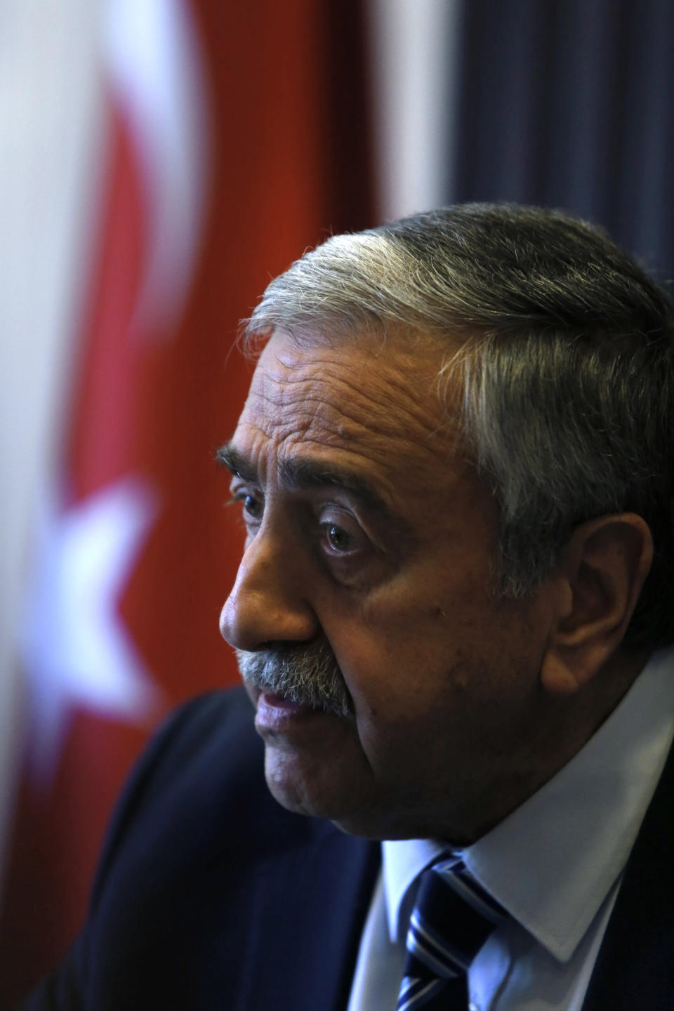 FILE - In this Monday, April 4, 2016 file photo, Turkish Cypriot leader Mustafa Akinci sits in his office during an interview for the Associated Press in the Turkish breakaway north part of the divided capital Nicosia in this ethnically Mediterranean island of Cyprus. Turkish Cypriots will vote Sunday Oct. 11, 2020 to choose a leader who will explore, with rival Greek Cypriots, whether there's enough common ground left for a deal to end the island's decades of ethnic division. (AP Photo/Petros Karadjias, File)