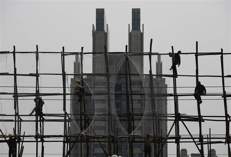 Labourers work on the scaffolding of a construction site for a new residential building in Beijing