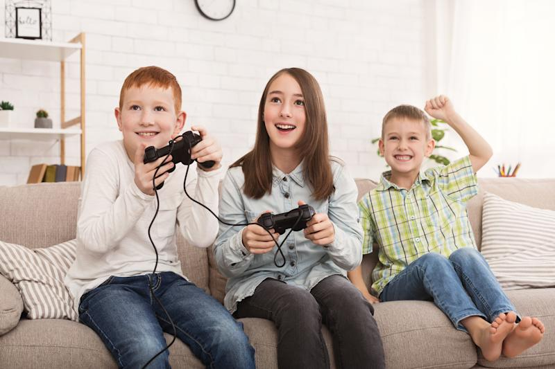 Three kids playing video games on the couch