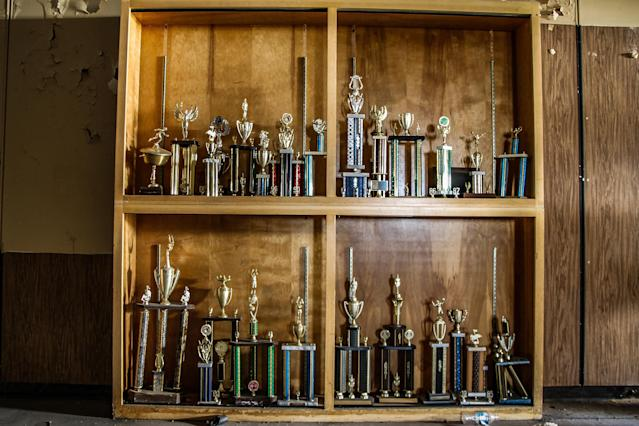 <p>The school trophy cabinet still holds sporting accolades from the school's history. The school had been open for nearly 100 years before closing. (Photo: Leland Kent/Caters News) </p>