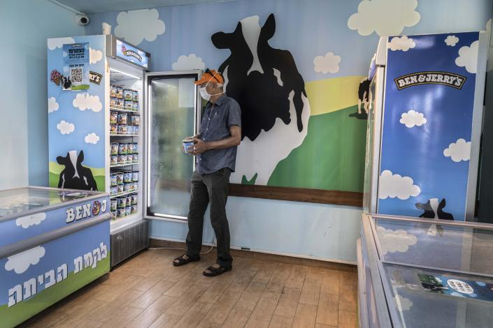"""FILE - In this Tuesday, July 20, 2021 file photo, an Israeli shops at the Ben & Jerry's ice-cream factory in the Be'er Tuvia Industrial area, southern Israel. Alan Jope the CEO of Unilever on Thursday, July 22, 2021, said the global consumer goods giant remains """"fully committed"""" to doing business in Israel, distancing himself from this week's announcement by the company's Ben & Jerry's ice cream brand to stop serving Israel's West Bank settlements. Jope gave no indication that Unilever would force Ben & Jerry's to roll back its controversial decision. (AP Photo/Tsafrir Abayov, File)"""