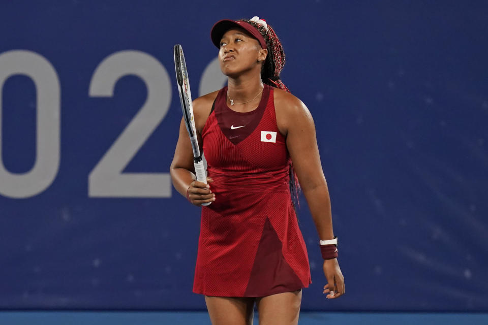 Naomi Osaka, of Japan, reacts after losing a point to Marketa Vondrousova, of the Czech Republic, during the third round of the tennis competition at the 2020 Summer Olympics, Tuesday, July 27, 2021, in Tokyo, Japan. (AP Photo/Seth Wenig)