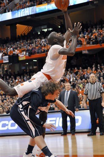 Syracuse's Baye Moussa Keita is fouled while grabbing a rebound over Monmouth's Christian White during the first half of an NCAA college basketball game in Syracuse, N.Y., Saturday, Dec. 8, 2012. (AP Photo/Kevin Rivoli)