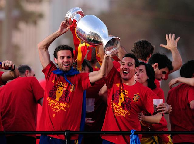 MADRID, SPAIN - JULY 02: Juan Mata (L) and Santi Cazorla of Spain holds the UEFA EURO 2012 trophy aloft while celebrating with fellow players as they parade the UEFA EURO 2012 trophy on a double-decker bus on July 2, 2012 in Madrid, Spain. Spain beat Italy 4-0 in the UEFA EURO 2012 final match in Kiev, Ukraine, on July 1, 2012. (Photo by Denis Doyle/Getty Images)