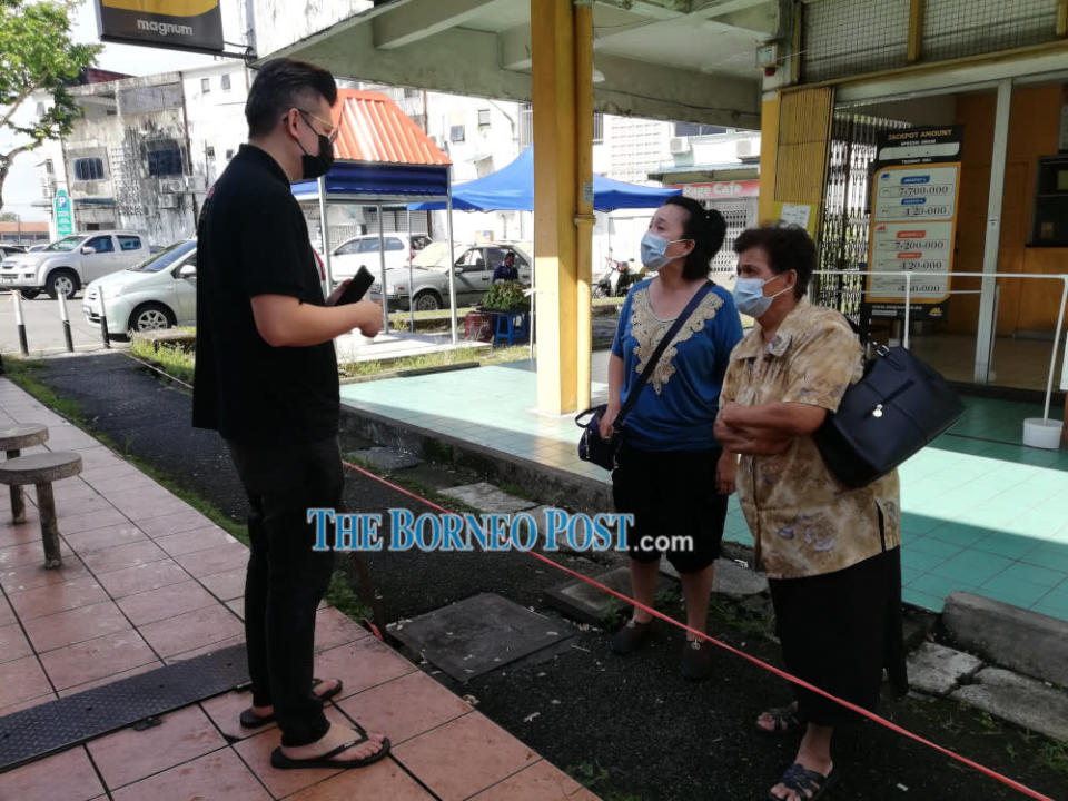 File picture shows Bandar Kuching MP Dr Kelvin Yii speaking to two senior citizens about the vaccination programme. — Borneo Post Online pic