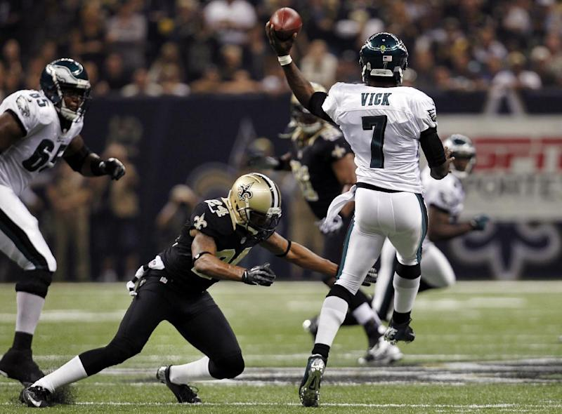 Philadelphia Eagles quarterback Michael Vick (7) passes under pressure from New Orleans Saints cornerback Corey White (24) during the first half of an NFL football game at Mercedes-Benz Superdome in New Orleans, Monday, Nov. 5, 2012. (AP Photo/Gerald Herbert)