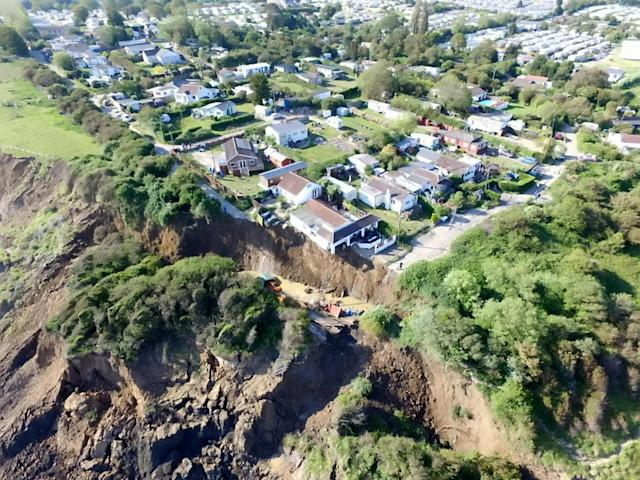 The house had been teetering on the edge of the cliff after a landslide on Sunday. (SWNS)