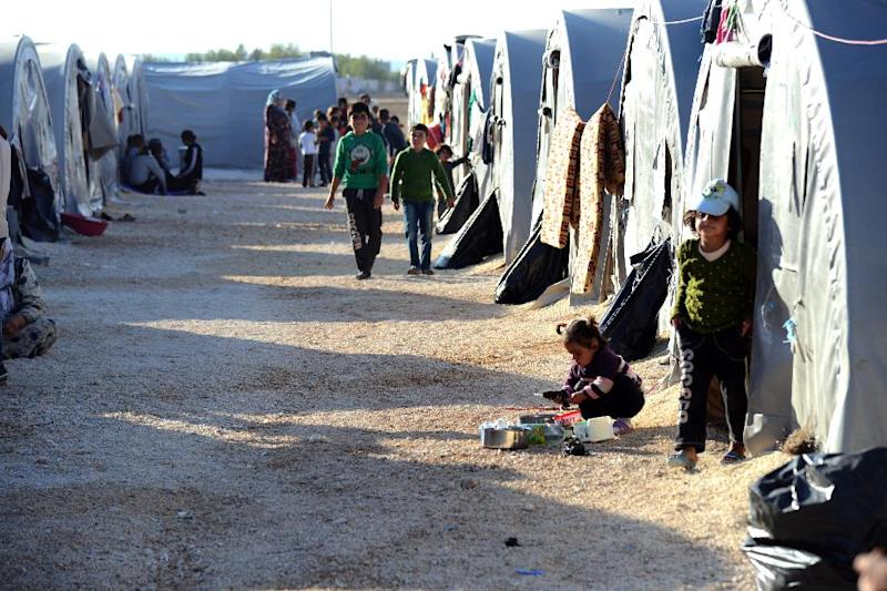 Children walk past tents on October 22, 2014 at Suruc Rojava refugee camp in Sanliurfa, where Sultan Muslim lives with her family, including newborn son Muhammed Obama Muslim (AFP Photo/Ilyas Akengin)