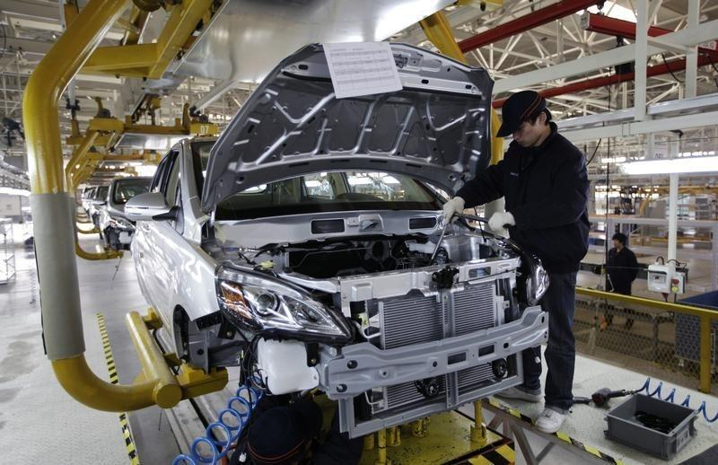 An employee works on the Beiqi E150EV car assembly line of Beijing Electric Vehicle Company