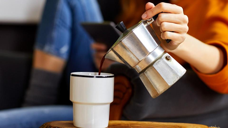 Midsection of young woman holding coffee maker while pouring coffee into cup.