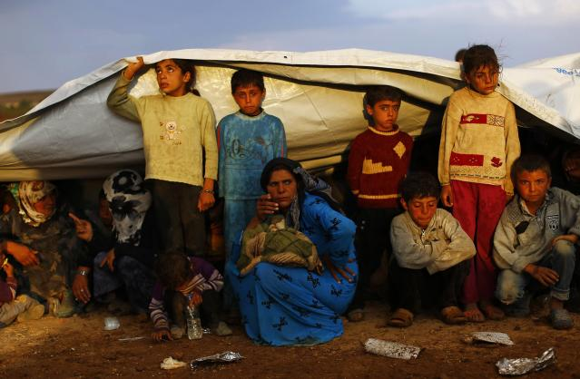 Syrian Kurdish refugees shield themselves from rain after crossing into Turkey from the Syrian border town Kobani, near the southeastern Turkish town of Suruc in Sanliurfa province October 2, 2014. More than 150,000 refugees have fled Kobani over the past two weeks alone, with a steady exodus continuing. Officials from Turkey's AFAD disaster management agency said some 4,000 crossed on Wednesday, and a similar figure the day before. REUTERS/Murad Sezer (TURKEY - Tags: POLITICS SOCIETY IMMIGRATION CIVIL UNREST CONFLICT TPX IMAGES OF THE DAY)