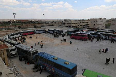 People, who were evacuated from the two rebel-besieged Shi'ite villages of al-Foua and Kefraya, stand near buses at insurgent-held al-Rashideen