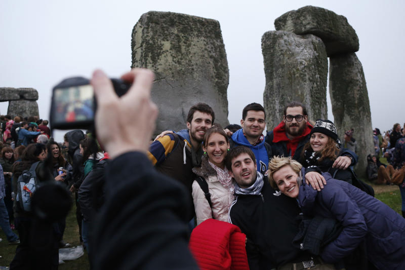 People take pictures during the summer solstice shortly after 04:52 am at the prehistoric Stonehenge monument, near Salisbury, England, Friday, June 21, 2013. Following an annual all-night party, thousands of New Agers and neo-pagans danced and whooped in delight at the ancient stone circle Stonehenge, marking the summer solstice, the longest day of the year. (AP Photo/Lefteris Pitarakis)